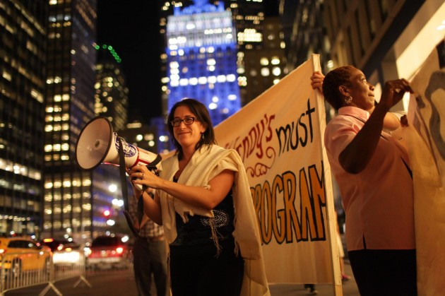 Rabbi Rachel Kahn-Troster holds a megaphone as she stands outside a protest of Wendy's.